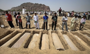 Pakistani Ahmadis bury their dead after a massacre