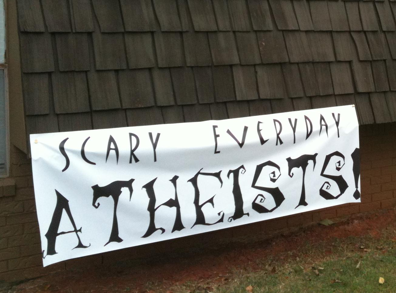 """[""""Scary Everyday Atheists"""" banner on the side of a house]"""